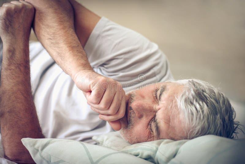 Больной старший человек в кровати стоковое фото rf
