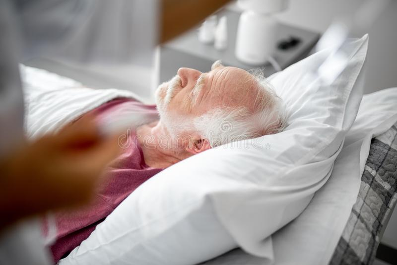 Больной старый пациент отдыхая в палате стоковое изображение