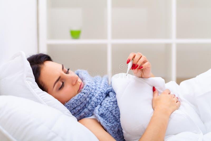 Больной холод уловленный женщиной, имеющ лихорадку и измеряющ Wi температуры стоковая фотография