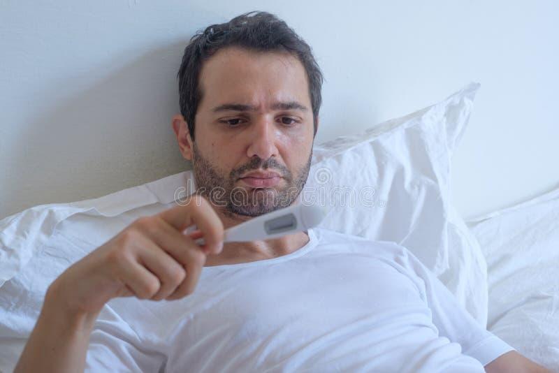Больной человек в температуре кровати измеряя и термометре смотреть стоковое фото