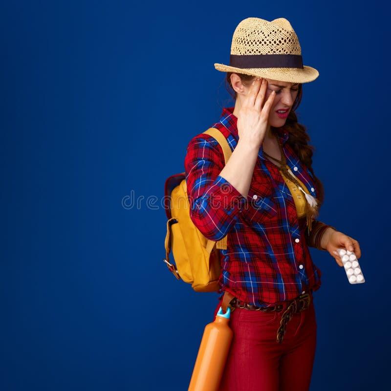 Больной hiker женщины с медициной в пакете волдыря имея головную боль стоковая фотография
