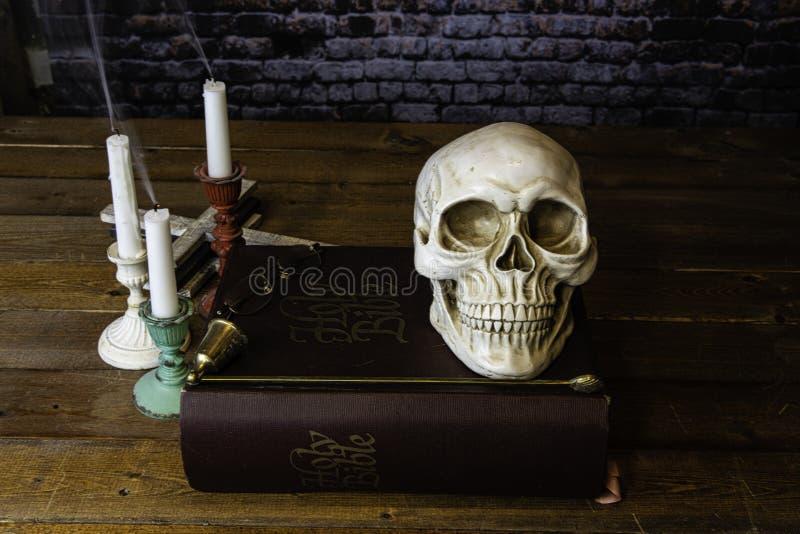 Большая античная библия с черепом и свечами курения стоковая фотография