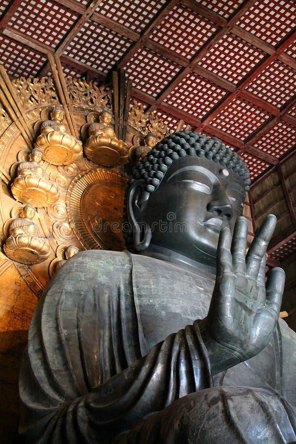 Большая бронзовая статуя Будды с правой рукой подняла в деревянном виске с фоном золота стоковая фотография