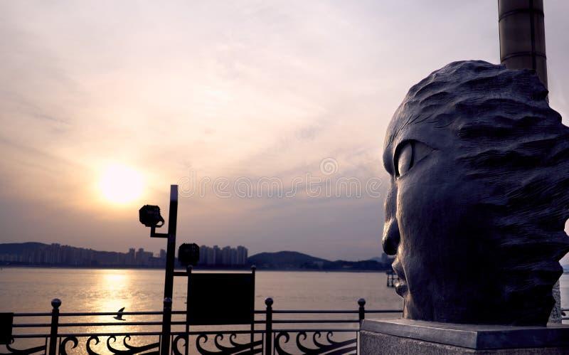 Большая главная форменная статуя смотря на океан захода солнца в обще стоковая фотография rf