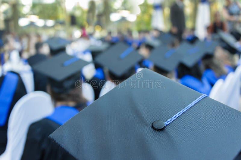 Большая группа в составе студенты одела в мантиях и нося крышках стоковые фотографии rf