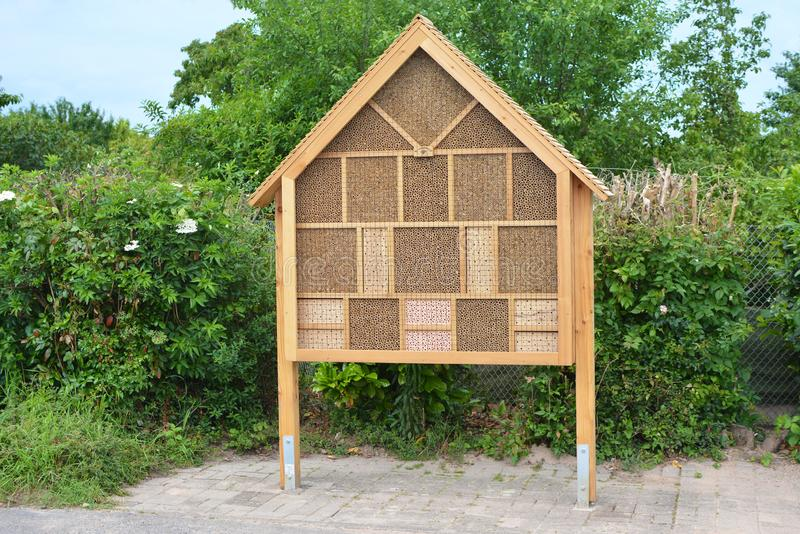 Большая деревянная структура гостиницы дома насекомого созданная для того чтобы обеспечить укрытие для насекомых как пчелы для пр стоковая фотография rf