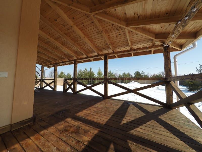 большая деревянная терраса в традиционном шале с панорамными окнами и сосновым лесом вокруг стоковая фотография