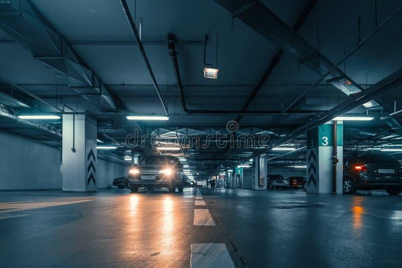 Большая зала с столбцами подземного гаража автомобиля с много автомобилей в современных моле или торговом центре внутрь стоковые изображения rf
