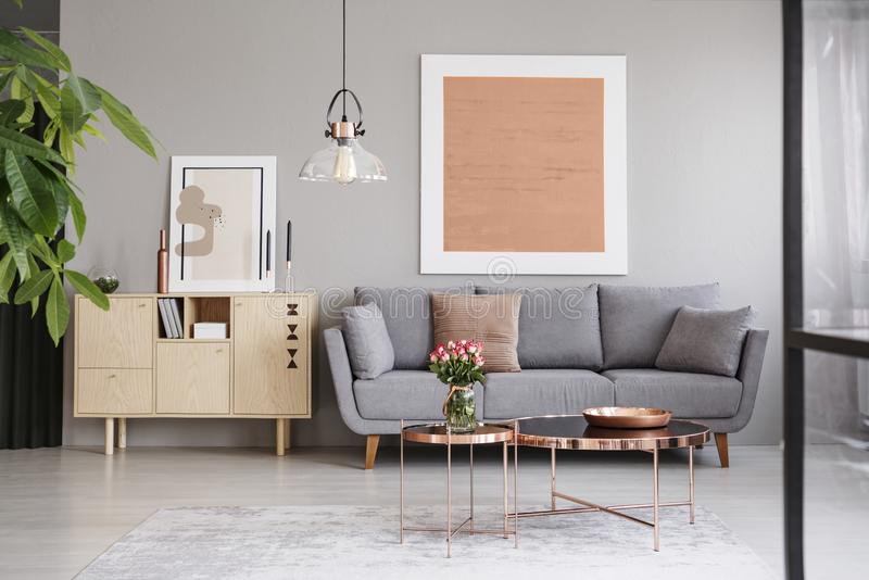 Большая картина на серой стене над элегантной софой с валиками в стильной живущей комнате с медной мебелью стоковое изображение rf