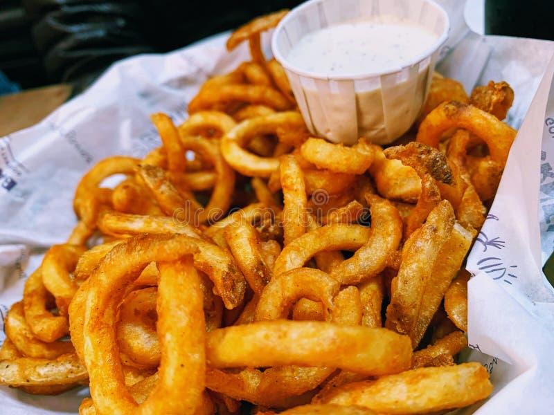 Большая корзина курчавых картофеля фри и шлихты ранчо стоковые изображения rf