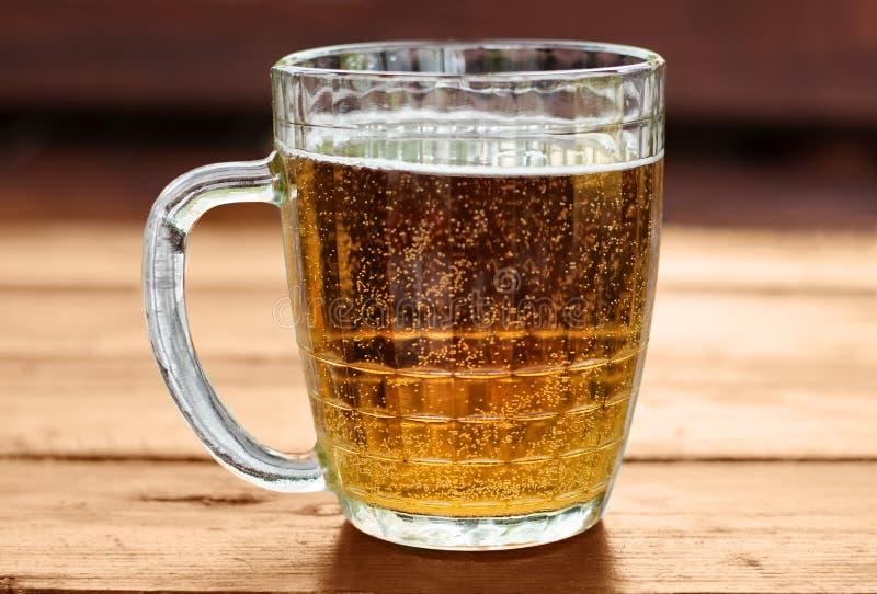Большая кружка пива с пеной и пузырей на деревянном столе стоковое фото