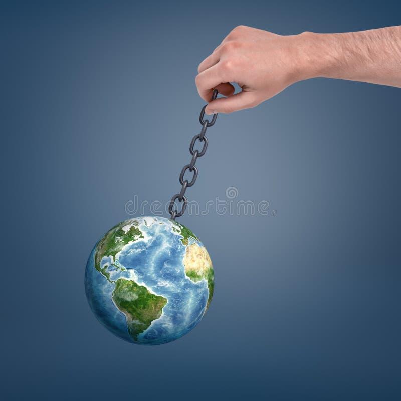 Большая мужская рука держа цепь металла при глобус земли вручая на ем и отбрасывать стоковая фотография rf