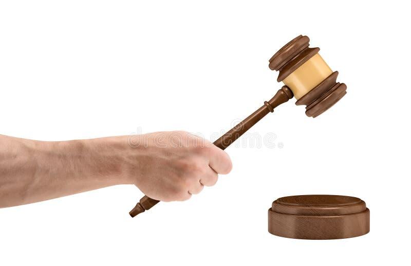 Большая мужская рука держит деревянный молоток судьи над круглым ядровым блоком изолированным на белой предпосылке стоковые фото