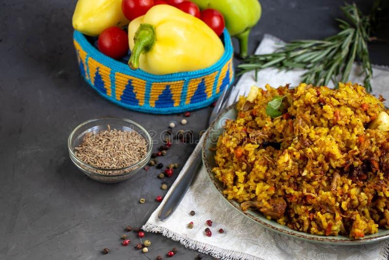 Большая плита заполненная с узбекским pilaf, рядом с томатами вишни, темная ткань, свежий перец во вручную связанной стойке стоковое фото