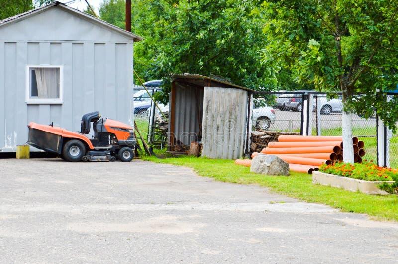 Большая профессиональная аграрная газонокосилка, трактор лужайки кося с травой, стойками около сарая инструмента стоковое изображение rf