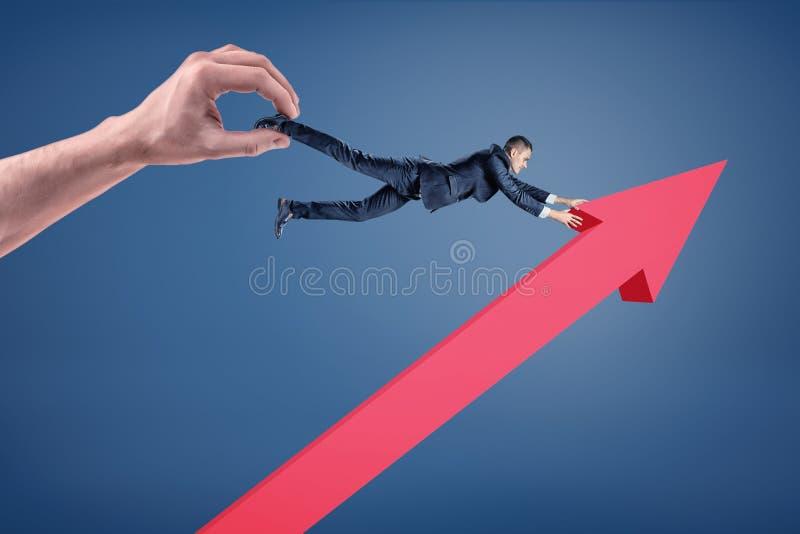 Большая рука держит бизнесмена который пробует держать на красную верхнюю указывая стрелку стоковая фотография