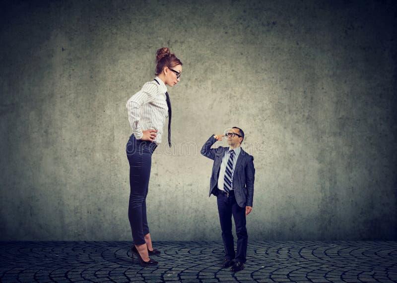 Большая сварливая коммерсантка стоя перед мелким бизнесом m стоковая фотография