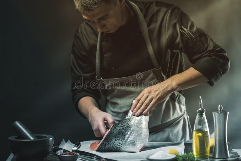 Большая семга в руках кашевара шеф-повара Он использует нож для того чтобы отрезать salmon филе стоковая фотография