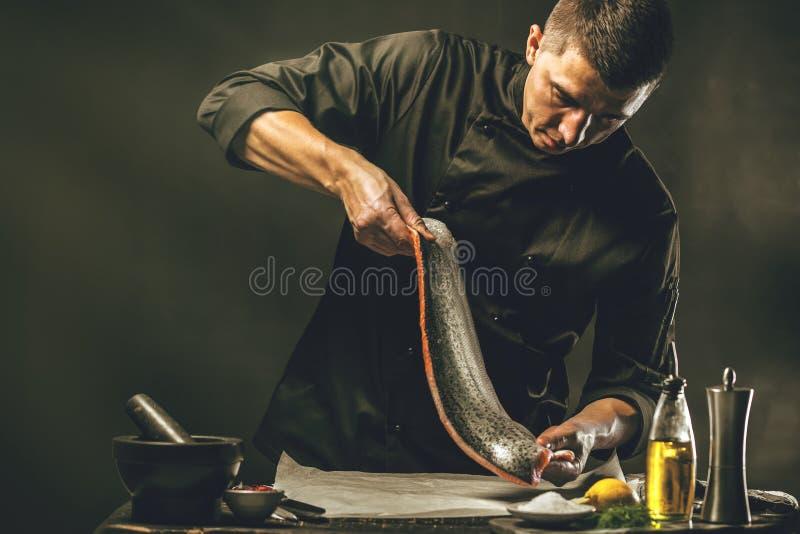 Большая семга в руках кашевара шеф-повара Он использует нож для того чтобы отрезать salmon филе стоковое фото