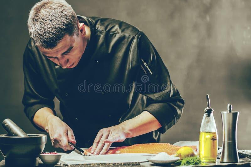Большая семга в руках кашевара шеф-повара Он использует нож для того чтобы отрезать salmon филе стоковые изображения