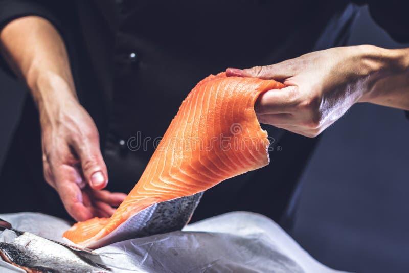Большая семга в руках кашевара шеф-повара Он использует нож для того чтобы отрезать salmon филе стоковые изображения rf
