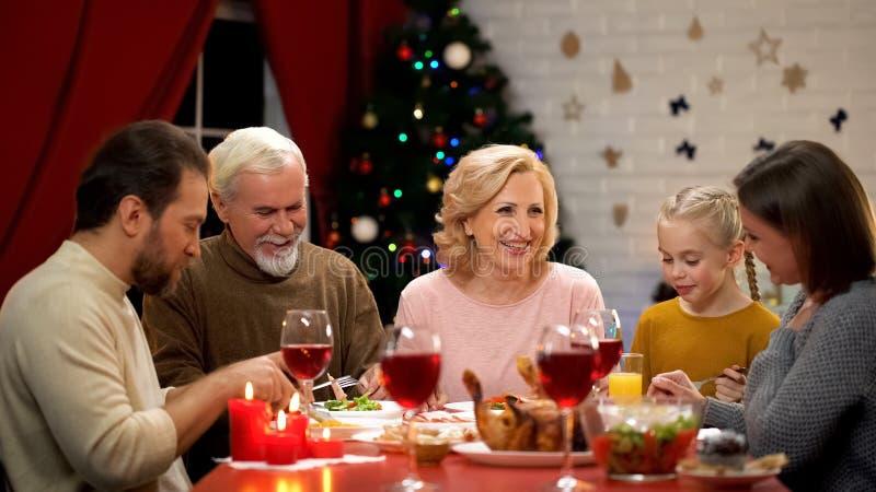 Большая семья есть обедающий Xmas, беседуя и усмехаясь, имеющ полезного время работы совместно стоковое изображение rf