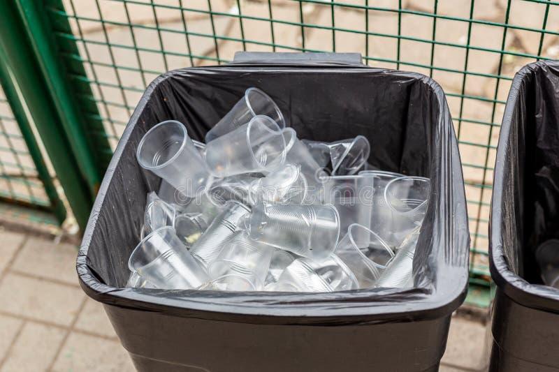Большая серая чонсервная банка trach вполне используемых пластичных прозрачных чашек Загрязнение окружающей среды и Мирового океа стоковая фотография