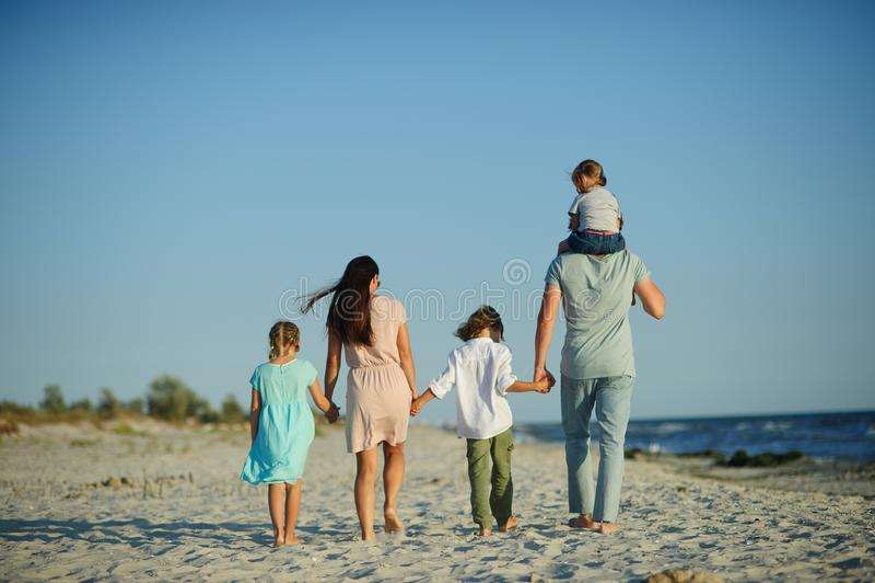 Большая счастливая семья идя на пляж Мама, папа и 3 дет Голубое небо, солнце, свежий ветер моря Удовольствие от природы стоковое изображение rf