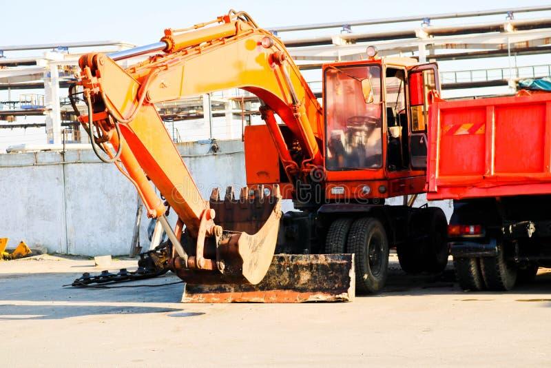 Большая тяжелая желтая оранжевая тележка с трейлером, самосвал и экскаватор с ковшом припаркованы в ряд на конструкции стоковое изображение