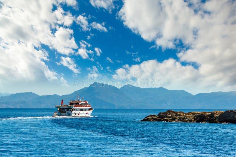 Большая яхта плавает близрасположенное скалистое побережье с деревьями в a стоковая фотография