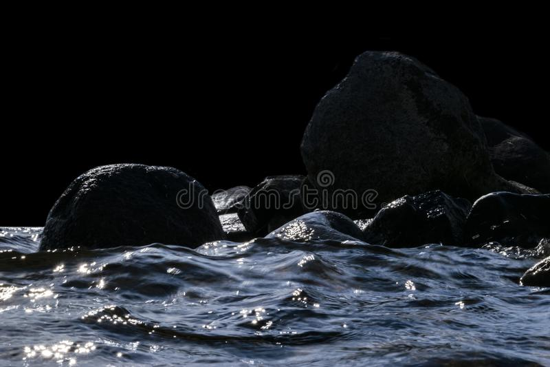 Большие ветреные волны брызгая над утесами Развевайте выплеск в озере изолированном на черной предпосылке Волны ломая на каменист стоковая фотография