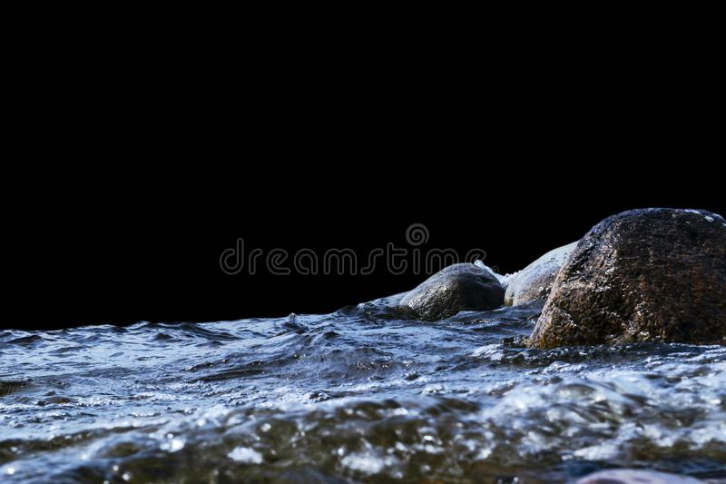 Большие ветреные волны брызгая над утесами Развевайте выплеск в озере изолированном на черной предпосылке Волны ломая на каменист стоковые фото