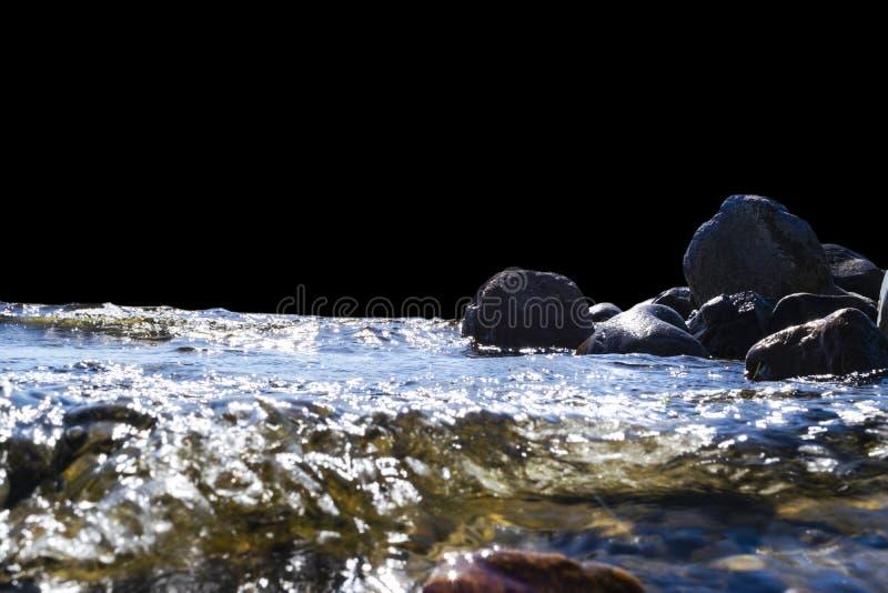 Большие ветреные волны брызгая над утесами Развевайте выплеск в озере изолированном на черной предпосылке Волны ломая на каменист стоковые изображения