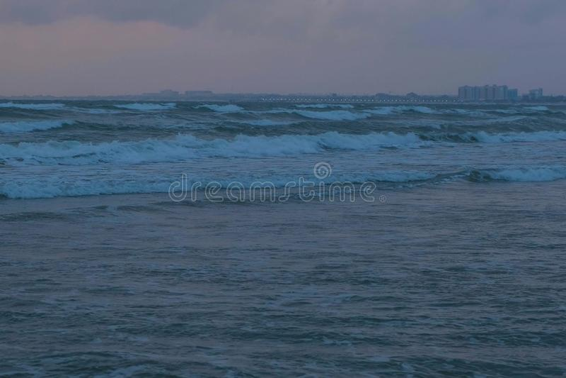 Большие волны пены шторма в море на заходе солнца в темном вечере в темноте Прибрежный город на предпосылке стоковое фото rf