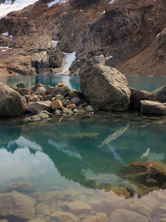 Большие камни лежа в озере гор бирюзы Гора отражая в поверхности воды Каменистый банк стоковое изображение rf