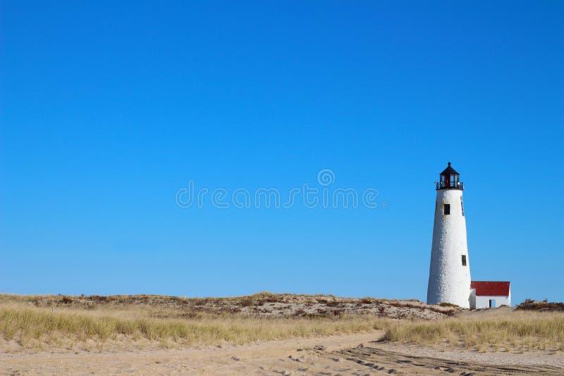 Большие МАМЫ Нантукета Массачусетса маяка света пункта с голубым небом, травой пляжа и дюнами и песком стоковые фотографии rf