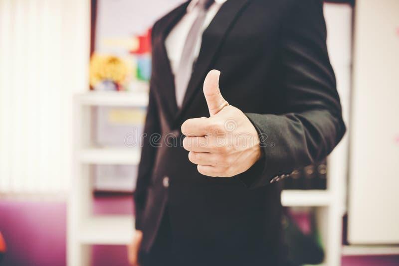 большие пальцы руки вверх Конец-вверх молодого показа бизнесмена стоковое изображение