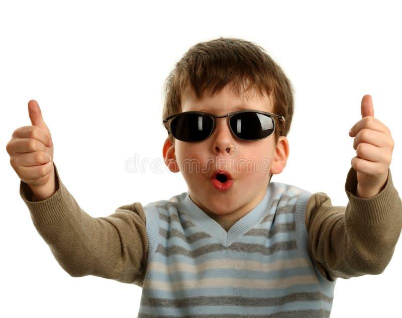 Большие пальцы руки вверх показанные счастливым молодым мальчиком на стеклах стоковое фото rf