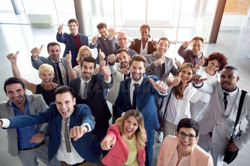Большие пальцы руки вверх по усмехаясь бизнесменам стоковые изображения rf