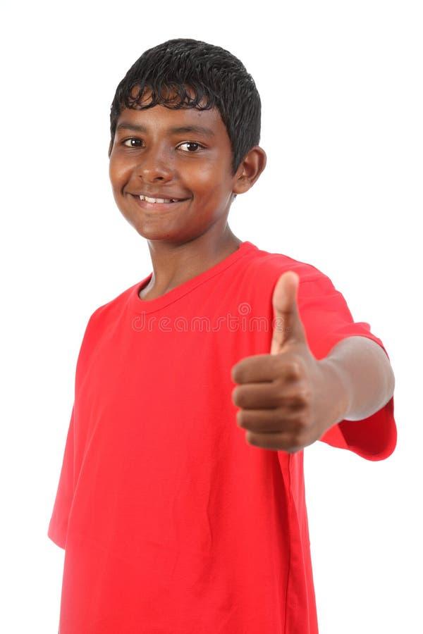 большие пальцы руки подростка студии усмешки мальчика поднимают детенышей стоковая фотография