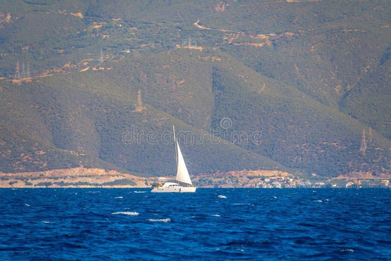 Большие прибрежные холмы и белая парусная яхта стоковое изображение
