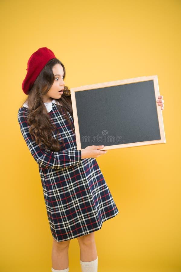 Большие продажи ребенок на желтой предпосылке E Интересная информация небольшой ребенк девушки с бакбортом школы, экземпляром стоковое изображение rf