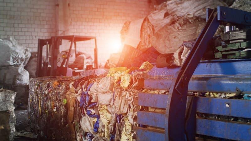 Большие связки отжатой погани из бумаги и пластиковых бутылок на заводе по переработке вторичного сырья, индустрии, внутренности, стоковая фотография