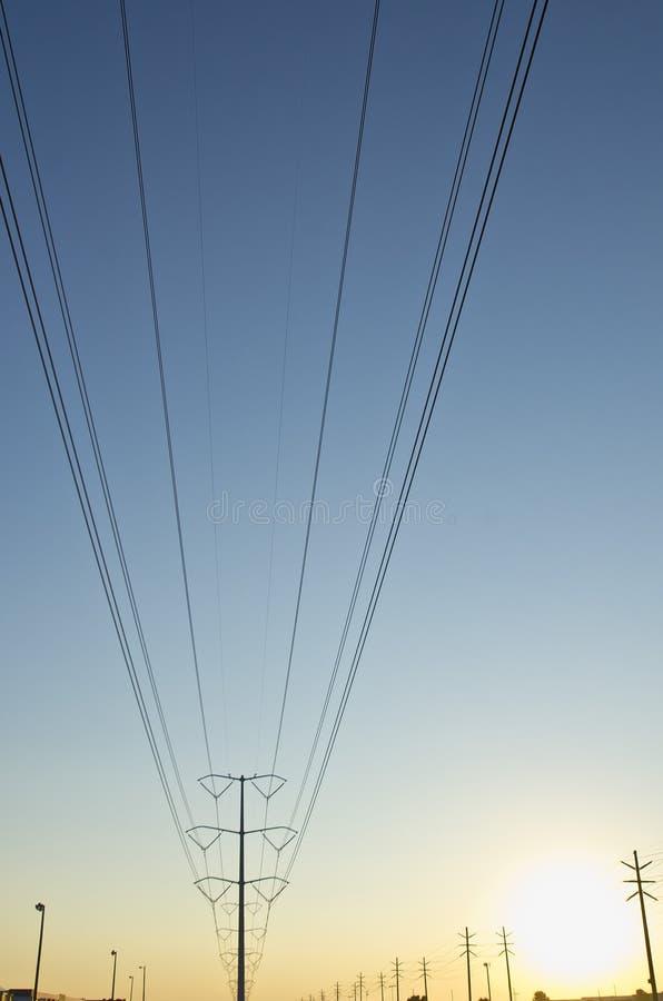 Большие сольные линия электропередач и поляк в голубом и желтом небе стоковое фото