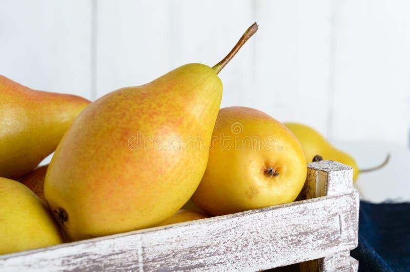 Большие сочные желтые груши в деревенской деревянной коробке плодоовощ на белой таблице стоковая фотография rf