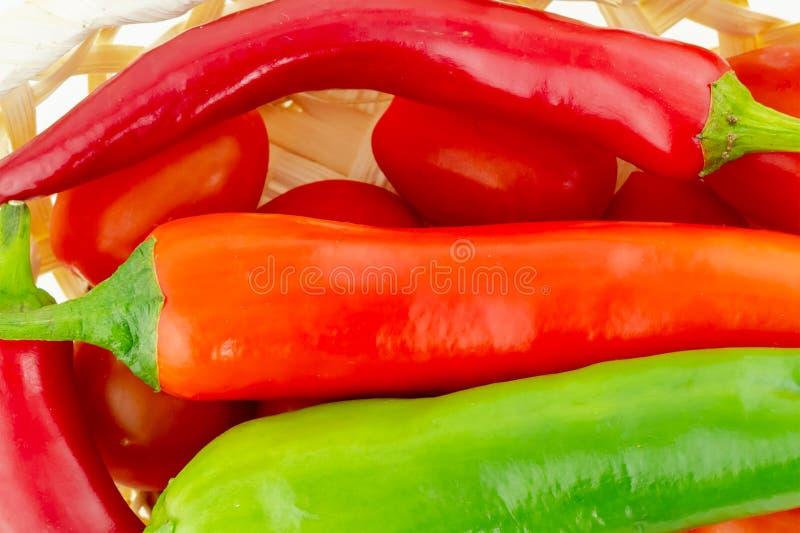 Большие стручки накаленного докрасна перца часть длинного зеленого овоща в конце-вверх корзины томата стоковые изображения