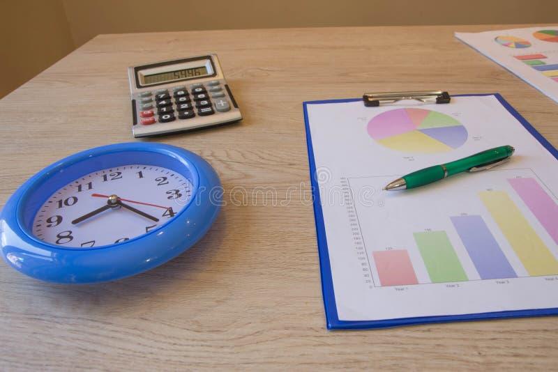 Большие часы, калькулятор, ручка, графики цвета на таблице Сбережения, финансы, экономика, концепция дела стоковые изображения rf