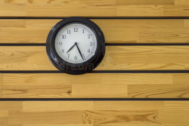 Большие черные круглые часы с концом-вверх стрелок на желтой деревянной стене планки горизонтальные прямые естественная поверхнос стоковое фото