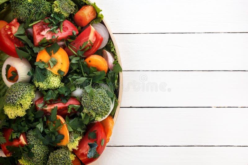Большинств полезные овощи брокколи, луки, чеснок, томаты, моркови отрезанные с зелеными цветами в черной плите стоковое изображение