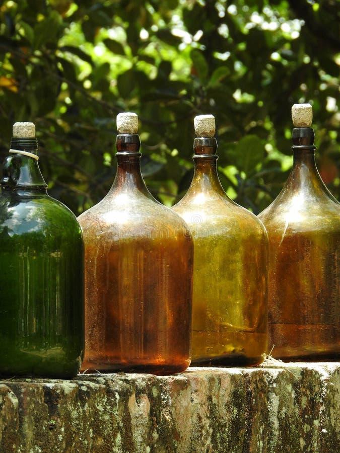4 больших бутылки с затворами пробочки, на каменной стене стоковые фото